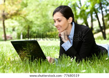 young pretty girl working on laptop outdoor, lying on grass,  caucasian 20 years old - stock photo