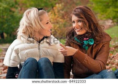 Young pretty girls gossiping at the autumn park - stock photo