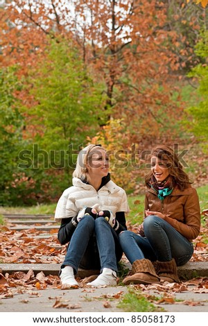Young pretty girls laughing at the autumn park - stock photo