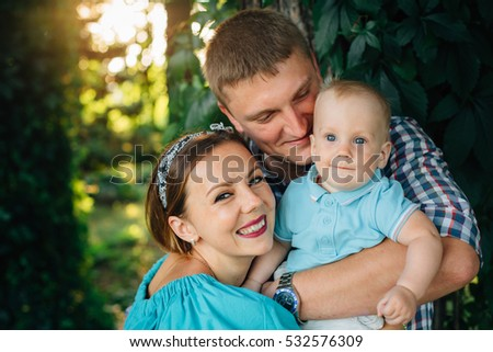Young pretty happy family  having fun in the park. Beautiful mother in turquoise dress with husband in checkered shirt and little cute baby kid boy playing outdoors. Happy parenting concept.