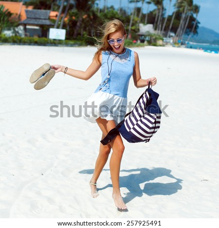 Young pretty happy running woman goes crazy fun on the beach in summer vacation time  - stock photo