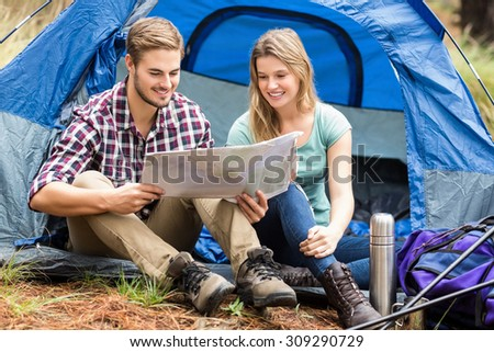 Young pretty hiker couple sitting in a tent looking at map in the nature