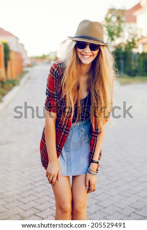 Young pretty hipster girl smiling and having fun outdoor in sunny day, wearing casual clothiers hat and sunglasses. - stock photo