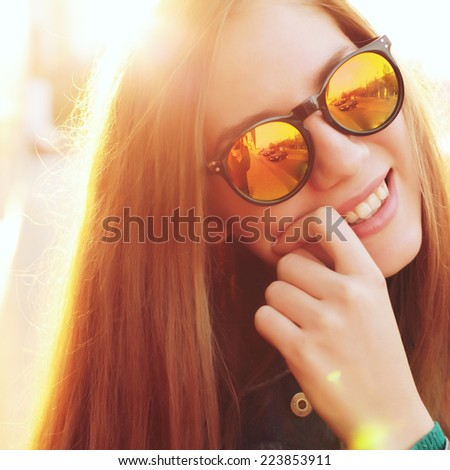 Young pretty hipster girl smiling and having fun outdoor in sunny day, wearing cool mirror stylish sunglasses. Photo toned style Instagram filters. - stock photo