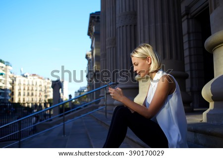 Young pretty hipster girl type massage in network on mobile phone and waits her friends in the fresh air, charming female international student searches in internet needed information for education - stock photo