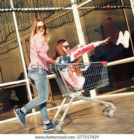 Young pretty hipster girls friends goes shopping in the city. Vintage lifestyle trendy portrait with a retro instagram filters - stock photo