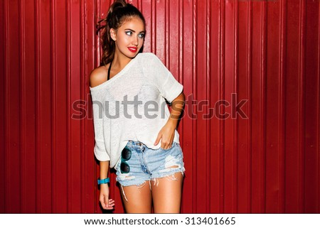 Young  pretty  hipster woman in trendy autumn clothes have fun and doing grimaces  near red  background  urban style  on  night party.  Bright flash ,  contrast color . - stock photo