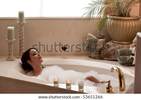 Young pretty lady relaxing in a bubble bath - stock photo