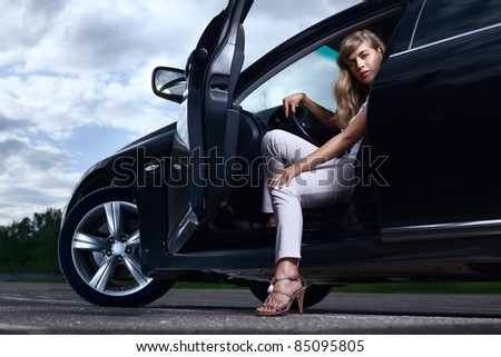 Young pretty lady with a modern luxury car - stock photo