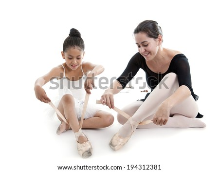 young pretty latin ballerina dance student girl and Classical Ballet teacher putting on and tying up her dance shoes isolated on a white background with copy space - stock photo