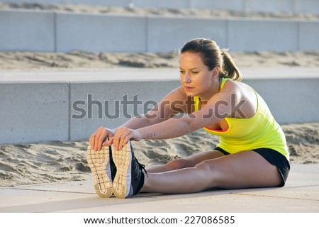 Young, pretty looking woman in sportswear, stretching and reaching her toes with her hand during an evening jog over the beach - stock photo