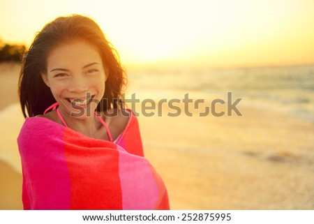 Young pretty mixed race Asian Caucasian model woman wrapped in towel standing in beach sunset. Smiling happy enjoying summer holiday travel vacation. Hawaii. - stock photo