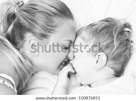 Young Pretty Mother And Cute Son Playing In The Bed - stock photo