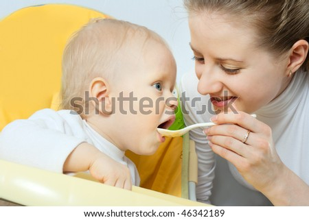 Young pretty mother feeding her baby - stock photo