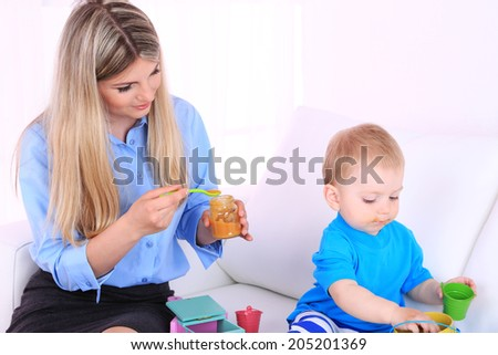 Young pretty mother feeding her son on sofa in room - stock photo
