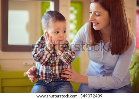 Young pretty mother playing and laughing with her baby son at home