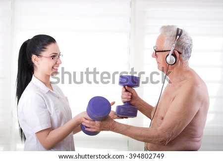 Young pretty nurse assisting old man in his therapy with dumbbells - stock photo