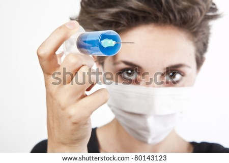 Young pretty nurse in mask with syringe