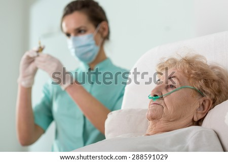 Young pretty nurse preparing to do injection to her patient - stock photo
