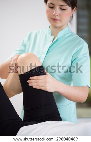 Young pretty physiotherapist flexing patient's knee - stock photo