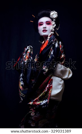 young pretty real geisha in kimono with sakura and decoration - stock photo