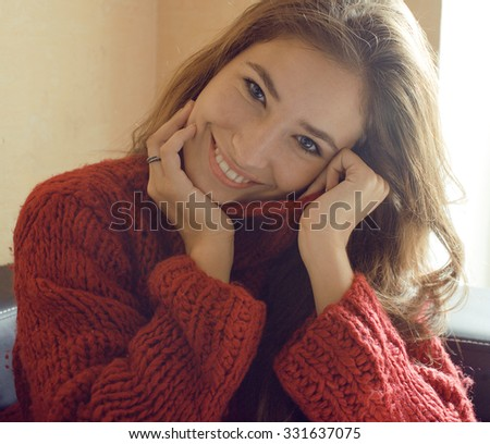 young pretty real woman in red sweater and scarf all over her face smiling at home, winter positive - stock photo