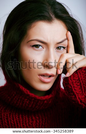 young pretty real woman in red sweater and scarf all over her face smiling at home, winter positive warm - stock photo