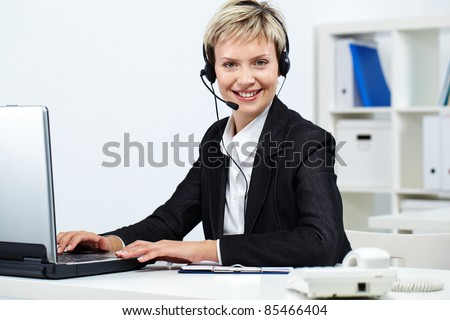 Young pretty receptionist with headset at computer looking at camera and smiling - stock photo
