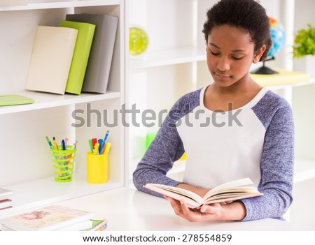 Young pretty schoolgirl sitting at the table and reading a book on colorful background.