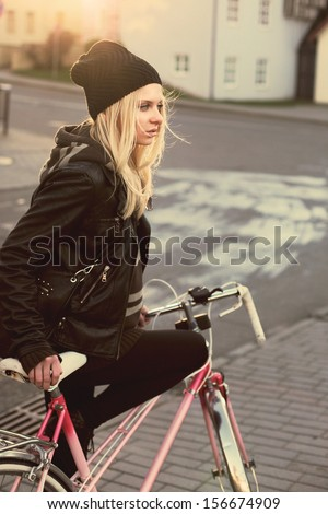 Young pretty sensual blond girl posing outdoor in winter with pink vintage bicycle  - stock photo