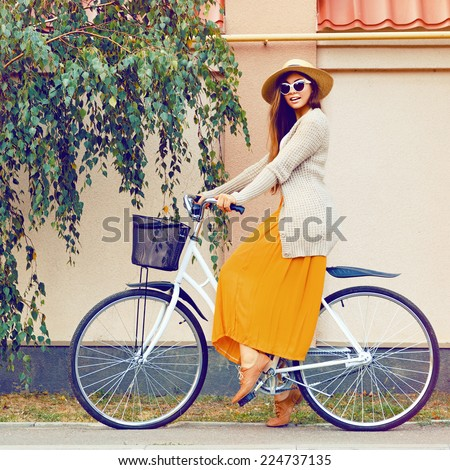 Young pretty sensual brunette girl, riding retro hipster bike, wearing vintage hat, maxi skirt, cozy warm jacket, and cat eye sunglasses. Soft vintage toned colors. - stock photo