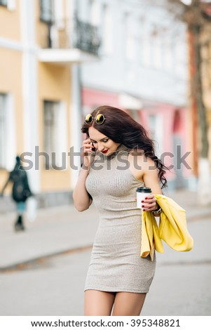 Young pretty sexy girl going crazy alone.Young woman at cafe drinks coffee and talking on the mobile phone.Young businesswoman talking on the phone. Bright yellow fashion jacket, gray spring dress. - stock photo