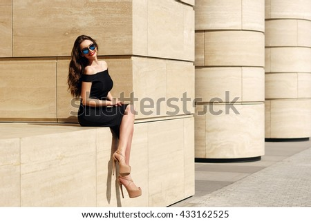 Young pretty sexy stylish girl in black dress and sunglasses sitting outdoors on a sunny day. Beautiful woman enjoying sun day and smiling