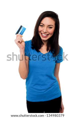 Young pretty smiling asian girl showing her credit card to the camera. - stock photo