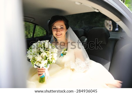 Young pretty smiling bride with bouquet sitting on the car - stock photo