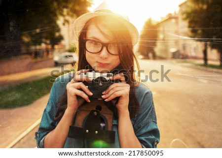 Young pretty smiling brunette woman outdoor summer closeup portrait portrait Sensual girl in white hat posing on the street in evening vintage style photo of photographer wit camera taking pictures  - stock photo