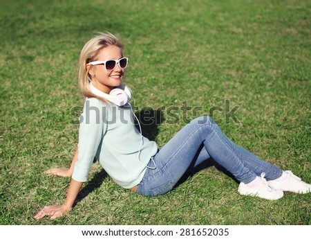Young pretty smiling girl sitting on the grass listens to music in the headphones and enjoys sunny day - stock photo