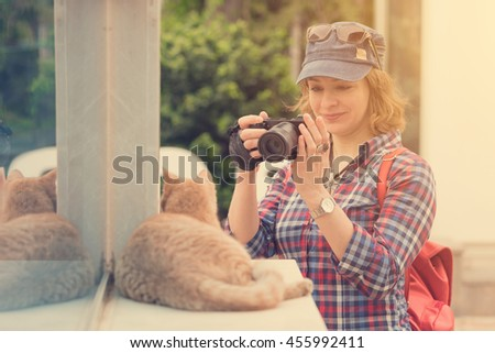 Young pretty smiling woman in a cap with a red backpack photographed ginger cat on the street. Sunny - stock photo
