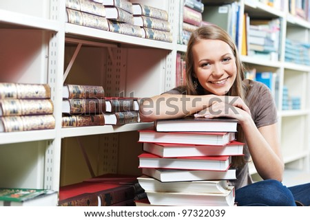 Young pretty smiling woman in a library with books at self-education - stock photo