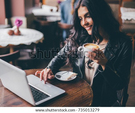 Young pretty spanish woman in cafe in city centre with tablet laptop