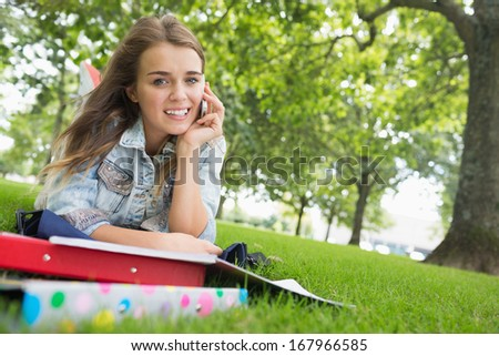Young pretty student lying on the grass on the phone on college campus - stock photo