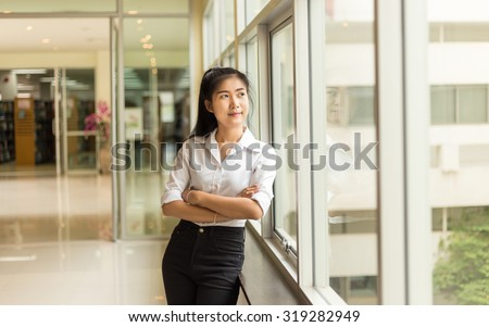 Young pretty student woman  in the bright modern Library indoors - stock photo