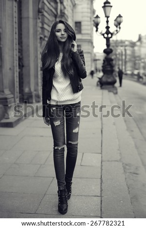 Young pretty stylish girl walking along the street. Monochrome full length portrait                               - stock photo