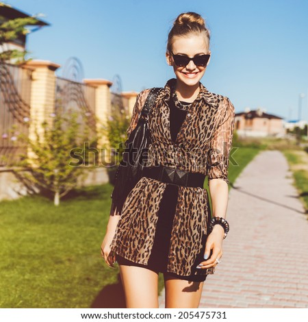 Young pretty stylish woman walking alone at beautiful summer day in short black dress and leopard printed shirt, wearing cat eye sunglasses, smiling an having fun. - stock photo