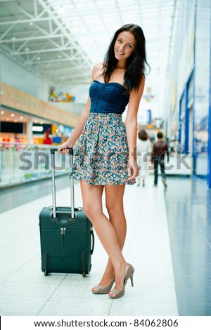 Young pretty stylish woman with luggage at the international airport. Waiting her flight at tax free shopping zone.