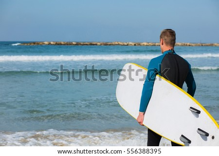 Young pretty surfer with wet suit boy holding yellow surfboard on the beach from behind.