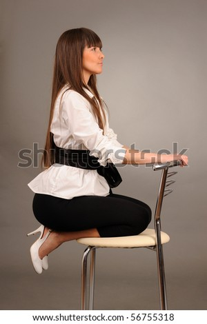 Young pretty swoman sitting in profile on a chair against gray background, studio shot. - stock photo