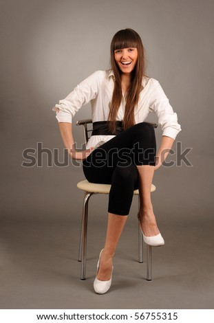 Young pretty swoman sitting on a chair against gray background, studio shot. - stock photo