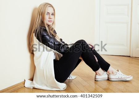 young pretty teenage blond girl sitting on floor at home despair sad alone, lifestyle concept - stock photo