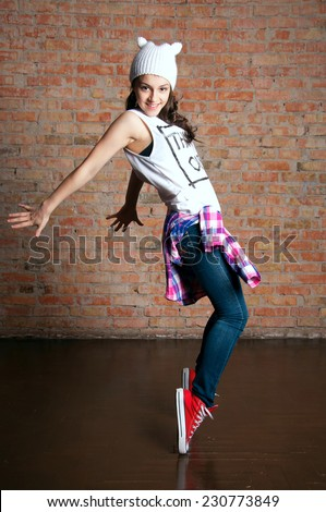 Young pretty teenage dancer standig on tiptoes, posing in studio against brick wall background - stock photo